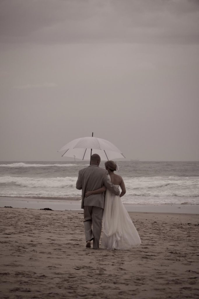 bride and groom walk on the beach with umbrella