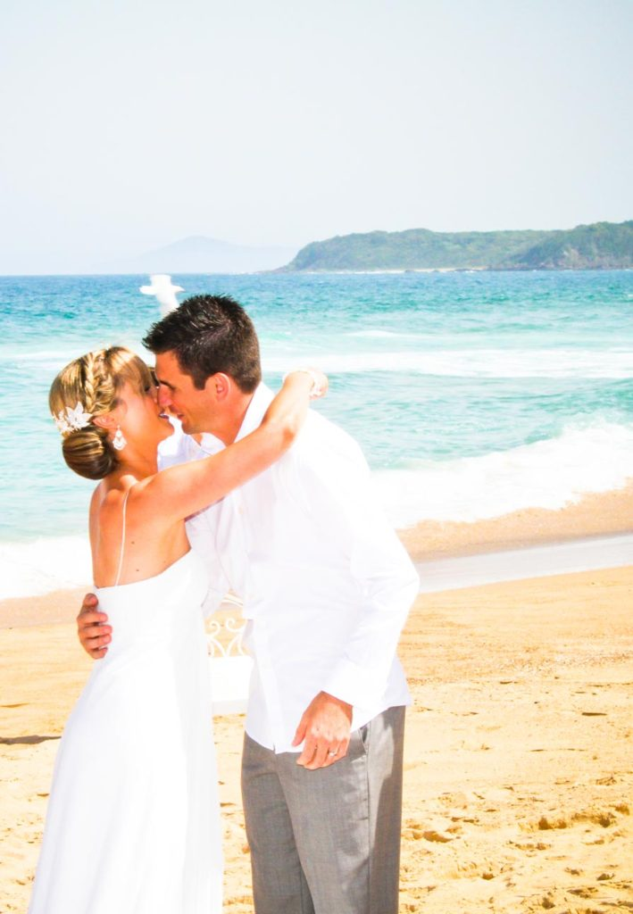 bride and grooms first kiss on the beach