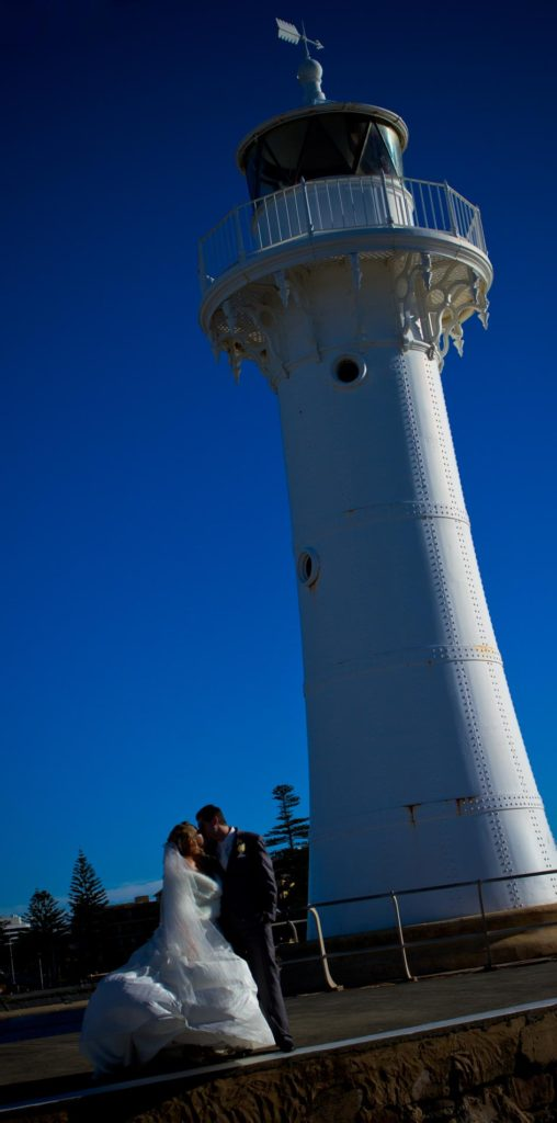 wedding couple shot in front of a lighthouse