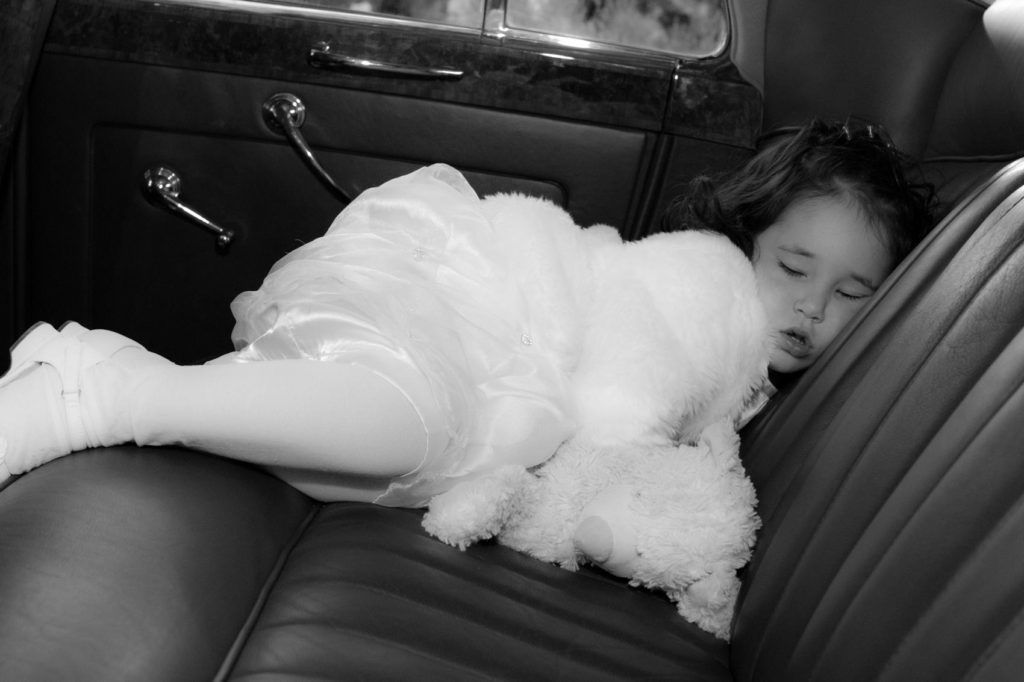 wedding shot of little girl asleep in a car