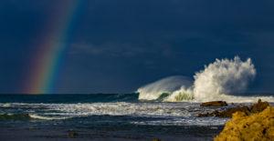 crashing waves with rainbow above