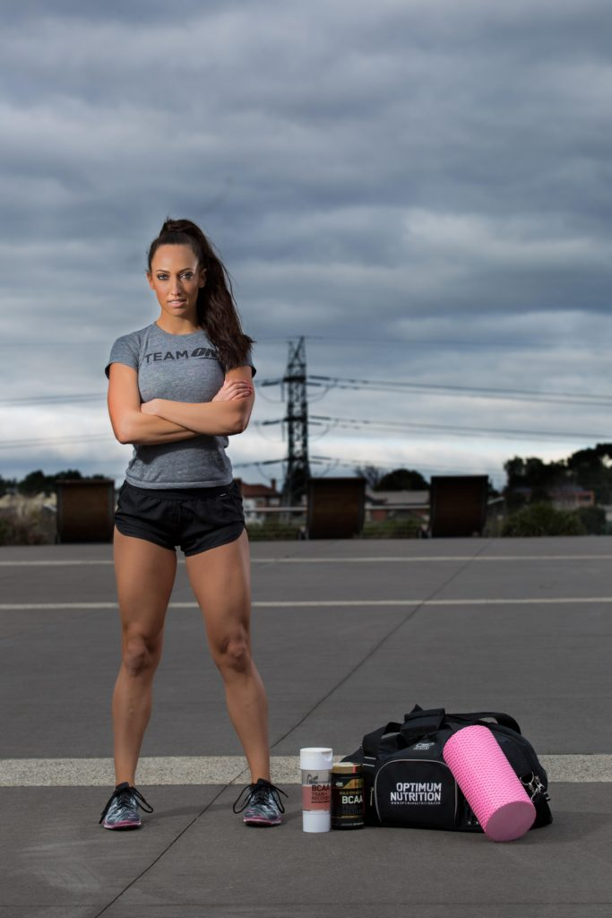 Fitness model power stance with gym bag