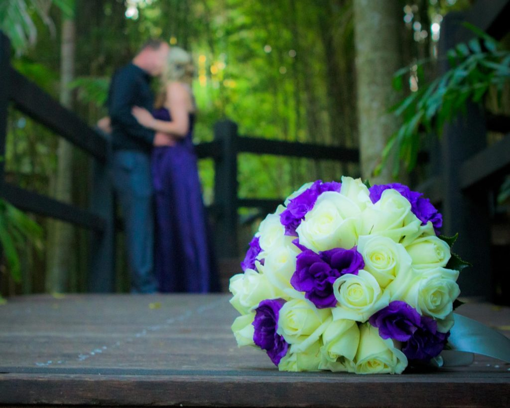 boquet in front of bride and groom kiss