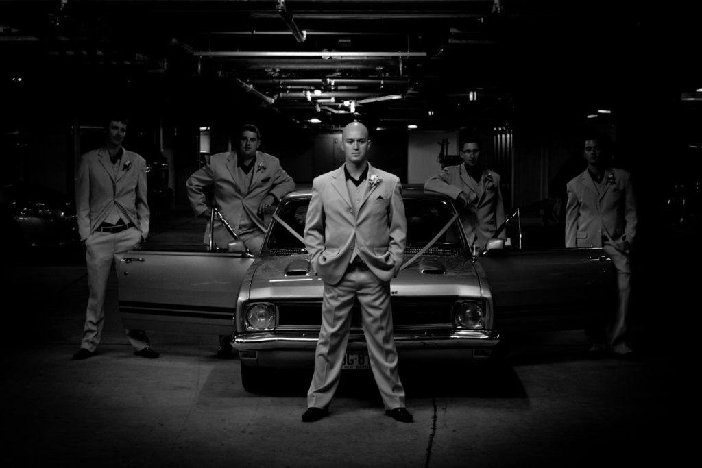 groomsmen shot in front of muscle car