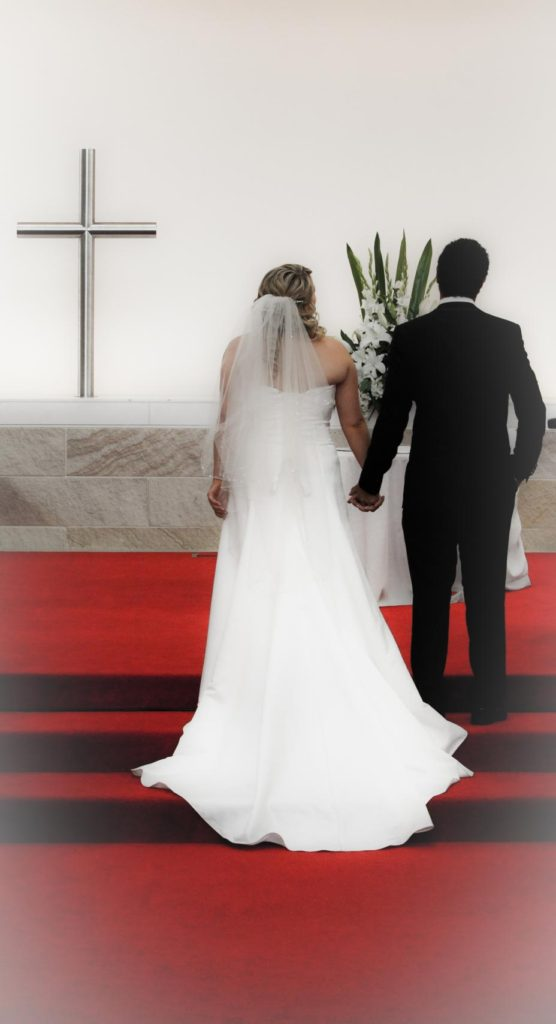 bride and groom hold hands in front of cross at alter