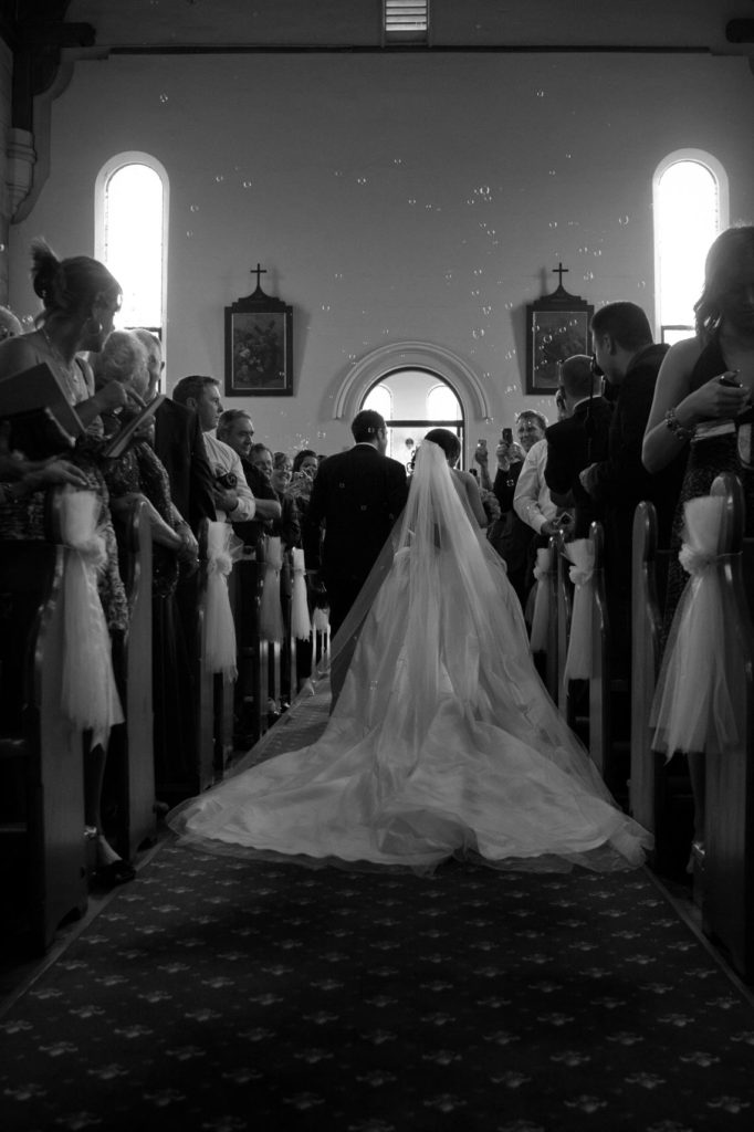 bride and groom exit church under bubbles