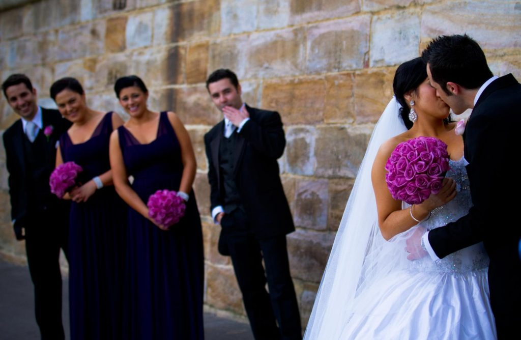 bride and groom kiss as bridal party look on