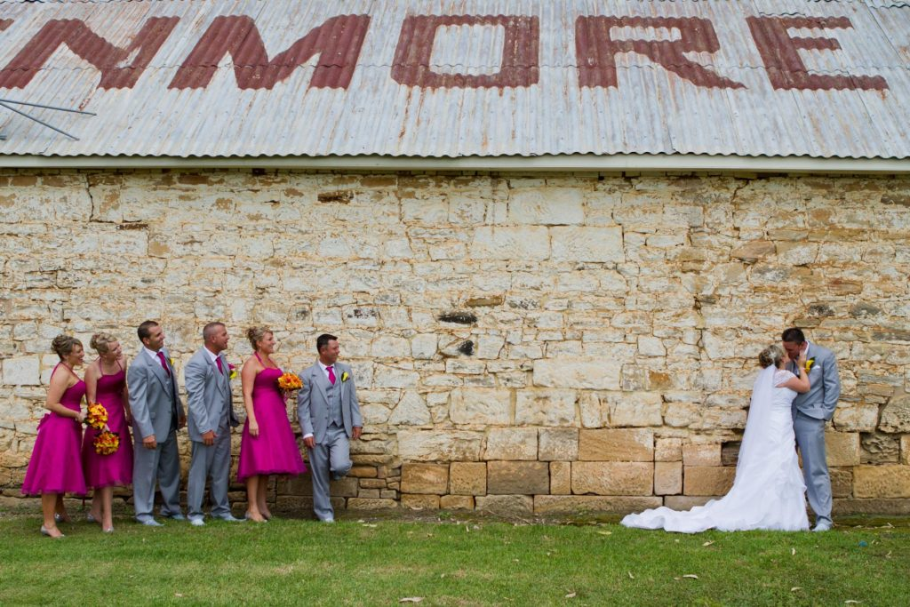 Wedding group shot in front of stone wall