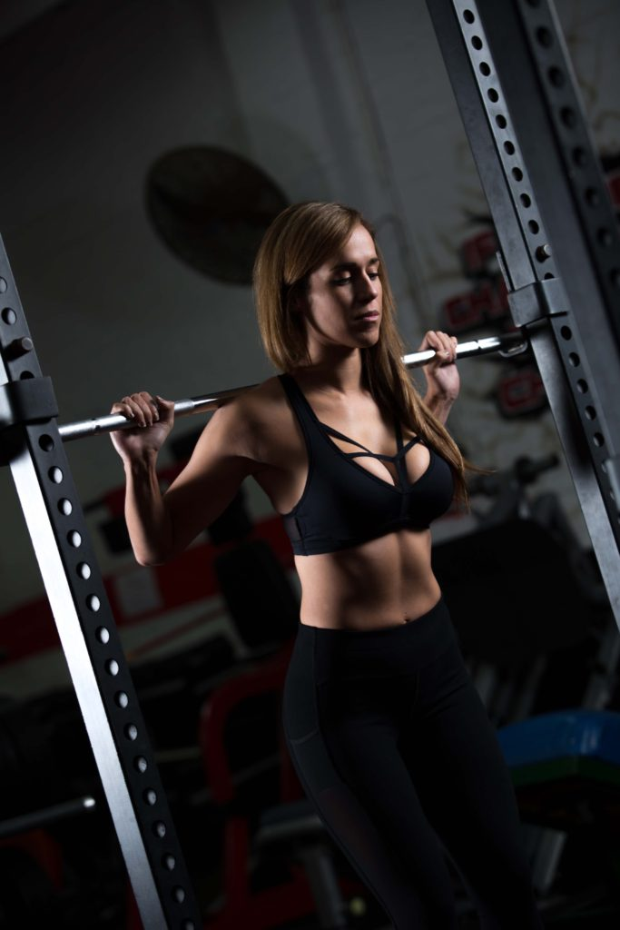 Fitness model barbell back squat in crop top
