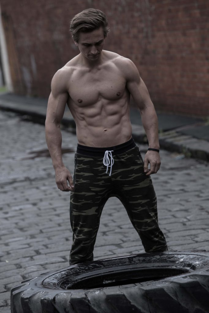 Male fitness model flipping tyre