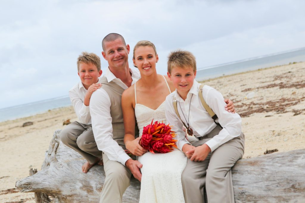 Wedding couple with two kids on the beach